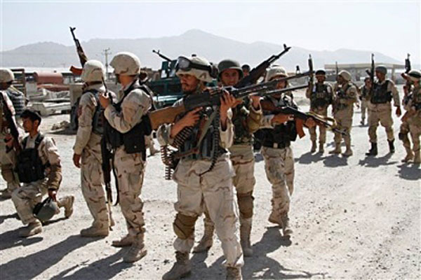 Afghan military soldiers stand guard as Taliban fighters attacked near Kabul airport, Afghanistan, Monday, June, 10, 2013. Seven heavily armed Taliban insurgents launched a pre-dawn attack.