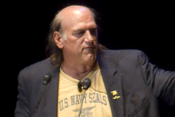 Jesse Ventura speaking at a podium.