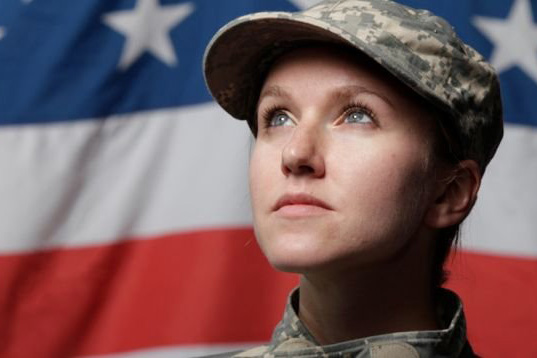 Female veteran in front of an American flag.