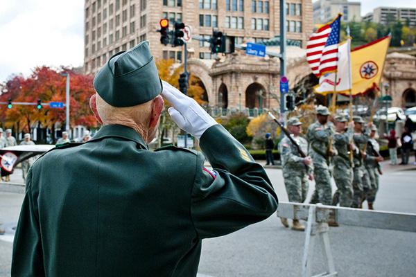 Retired veteran saluting soldiers.