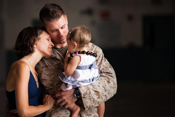 Servicemember holding family.