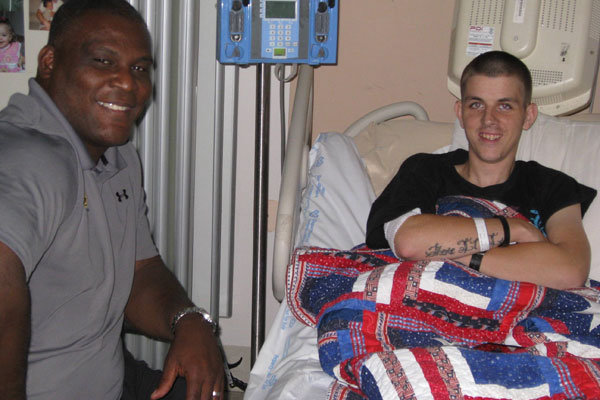 Col. Greg Gadson, director of the Army's Wounded Warrior Program, visits with Cpl. Jeremy D. Voels during a visit to the James A. Haley VA Hospital in Tampa.