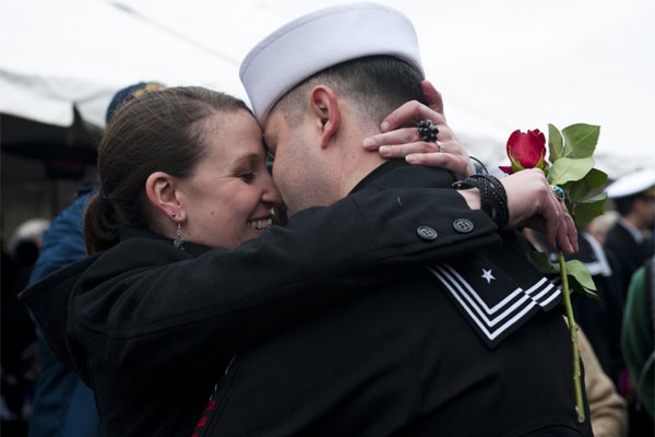 military couple embrace with rose