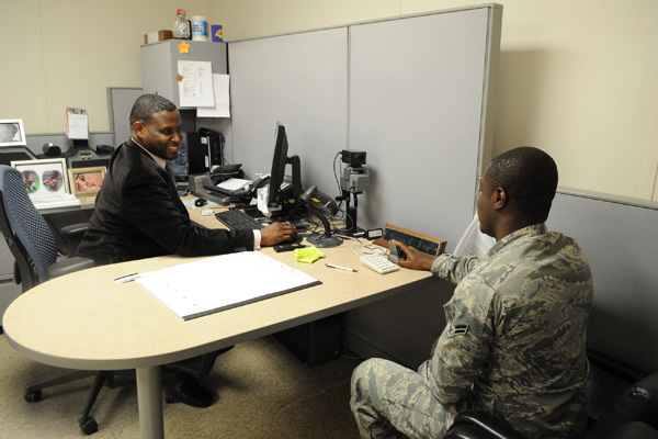 Service member having a discussion at a desk in front of a computer.