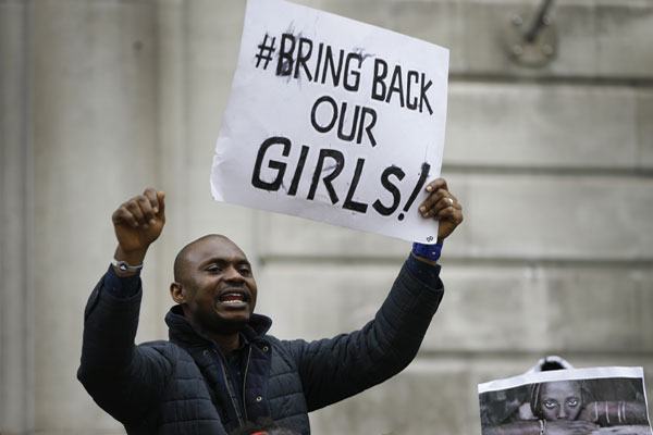 A demonstrator holds a banner, during a protest about the kidnapping of girls in Nigeria, near the Nigerian High Commission in London, Friday, May 9, 2014. (AP Photo/Kirsty Wigglesworth)