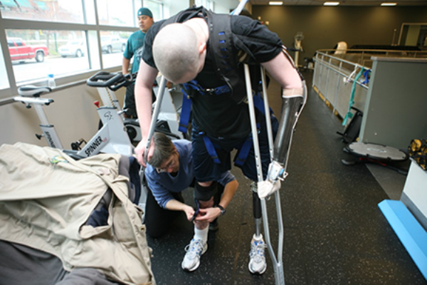 A patient in a Warrior Transition Unit receives assistance from a worker in this unda