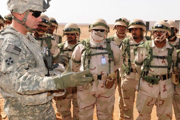 "US Army Lt. Col. Joshua Wright briefs Saudi troops during an April 2014 training exercise in Saudi Arabia. The Syrian foreign minister has warned that any Saudi or other foreign troops who enter Syria will ""return home in coffins."" (Army/Andrew Porch)"