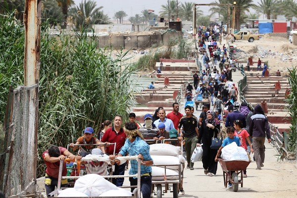 http://www.In this 2015 photo, Iraqi families fleeing violence in Ramadi walk across Bzebiz Bridge into Baghdad province. (Photo by Wathiq Khuzaie/UNICEF).com/army
