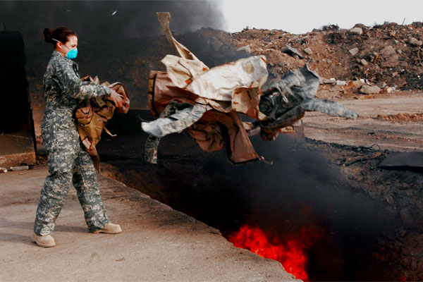 An airman tosses uniform items into a burn pit at Balad Air Base, Iraq, on March 10, 2008. (US Air Force photo/Julianne Showalter)