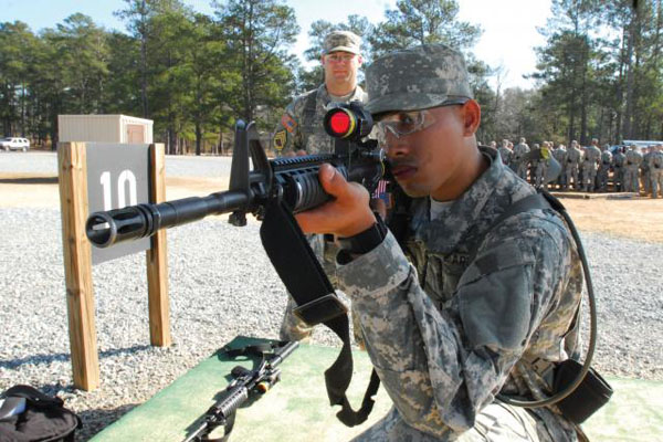 Army recruit during basic training aims a rifle.