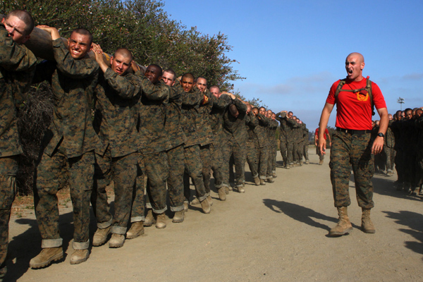 Marine recruits carrying a log