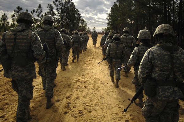 Recruits march along dirt road.