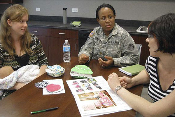 In this April 30, 2013, photo, Dianna Troyer, 27, of Clearwater, Fla.; Maj. LaToya Dunham, 35, from Dallas; and Tracey Levens, 29, of Luling, Texas, discuss cloth diapers in the new Third Army Nursing Center at Shaw Air Force Base, S.C.