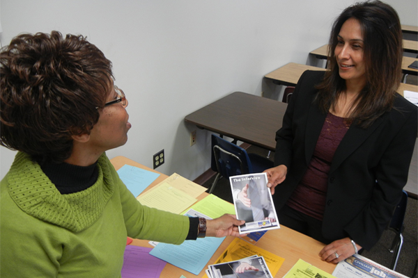 "Barbara West, program coordinator for the Family Member Employment Assistance Program offers Kishwar Speir, a Marine spouse, literature on interviewing after the ""'Acing the Interview""' workshop at Quantico. Ameesha Felton/Marine Corps"