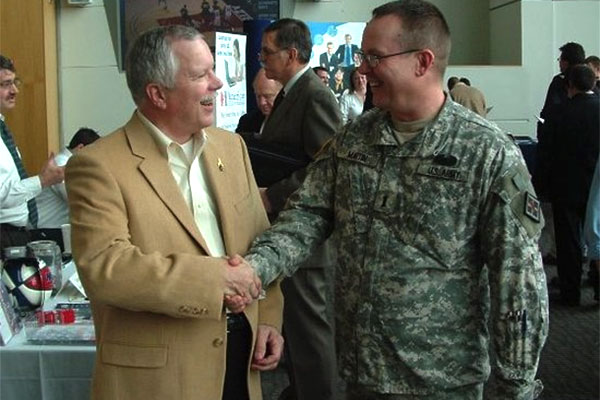 soldier shaking hads with employer at career fair