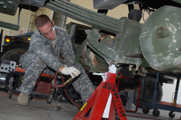 Army mechanic jacking vehicle.