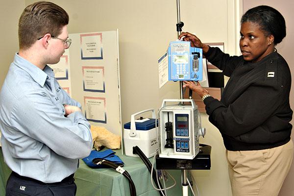Nurse Educator Lt. Melisa Gibbs explains how to operate various medical equipment to Hospitalman Apprentice Jason Lee. (U.S. Navy/Photographer's Mate 2nd Class Michael D. Winter)