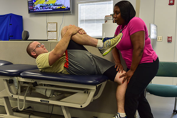 Virginia Lindsey, 1st Special Operations Medical Group physical therapy assistant, performs a quad muscle stretch on Tech. Sgt. James Kitchen at the physical therapy clinic on Hurlburt Field, Fla. (U.S. Air Force/Senior Airman Jeff Parkinson)