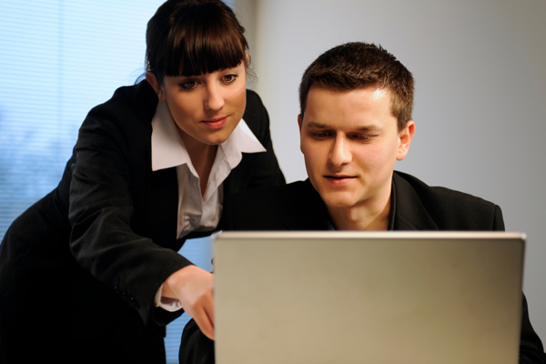 A man gets tutored from a professional about his laptop.