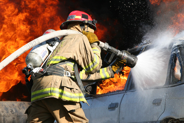 A firefighter hosing down a car that's on fire.
