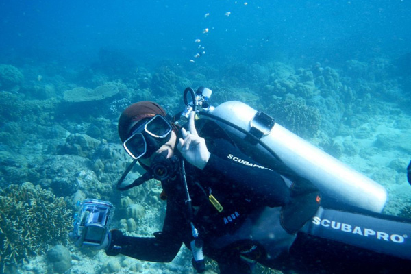 A scuba diver flashing the peace sign
