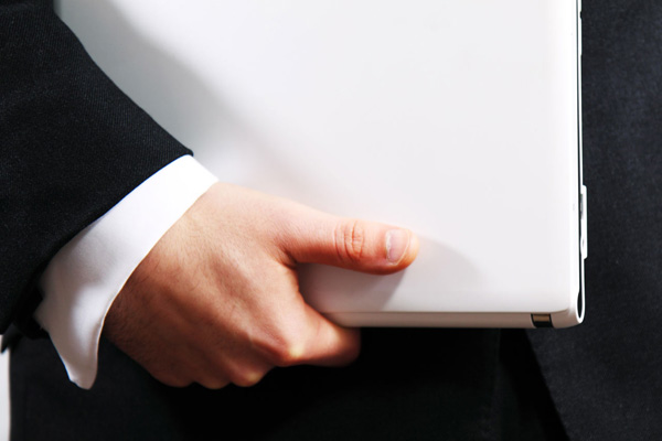 Businessman holding a white laptop.
