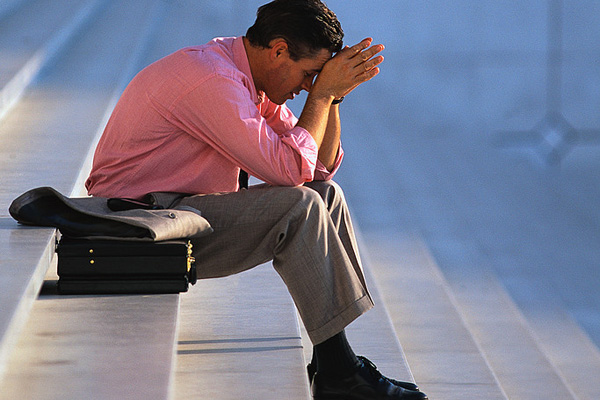 Depressed businessman sitting on stairs wearing a pink shirt.