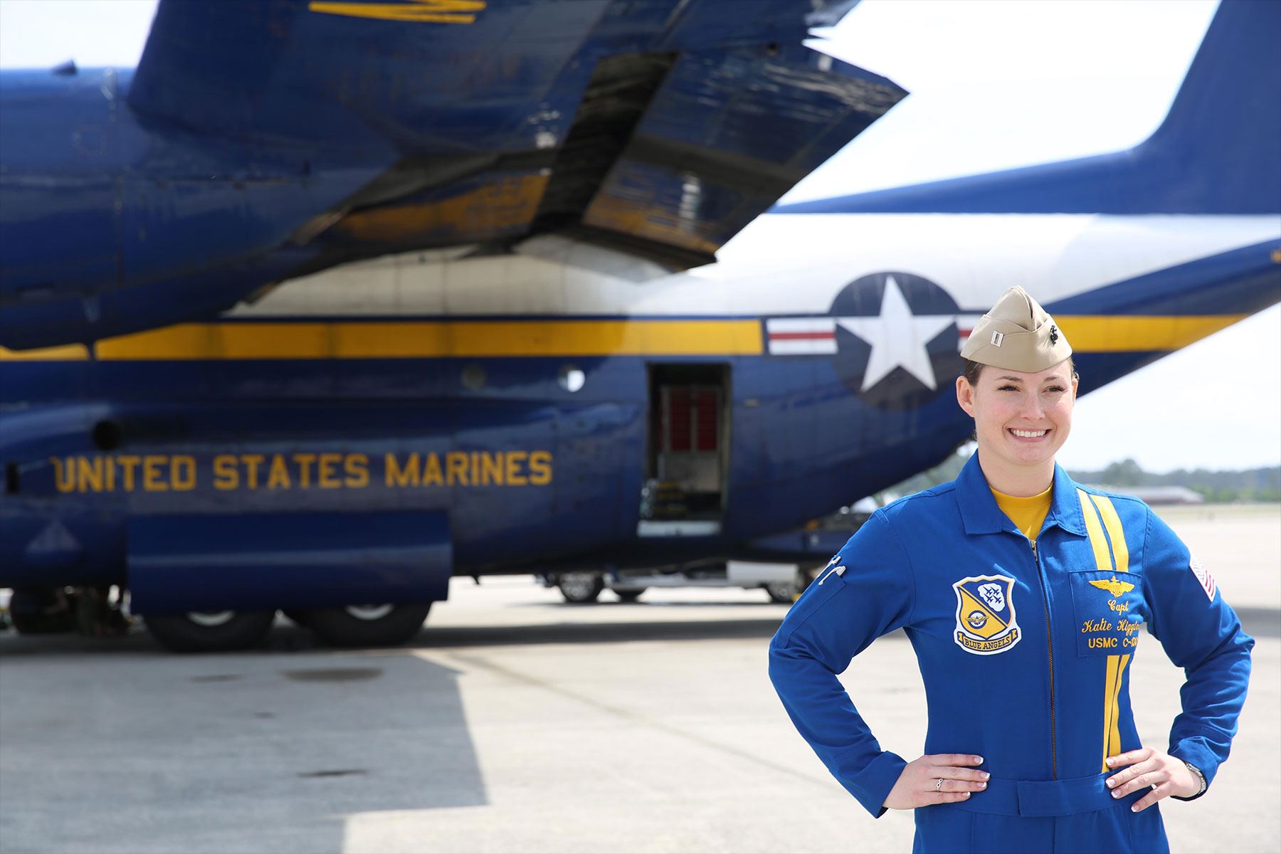 "Capt. Katie Higgins poses in front of ""Fat Albert"", the U.S. Navy Blue Angel's C-130J Super Hercules prior to the 2016 Marine Corps Air Station Cherry Point air show. (U.S. Marine Corps/Mackenzie Gibson)"