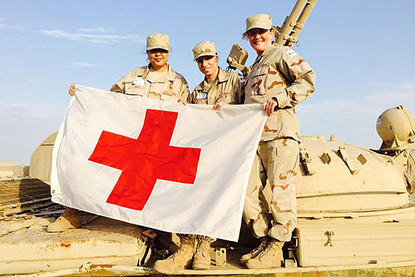 Navy wife Jennifer Cole (left) poses with her American Red Cross team at Camp Arifjan, Kuwait. Photo courtesy American Red Cross
